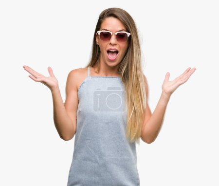 Photo for Beautiful young woman wearing sunglasses and denim dress very happy and excited, winner expression celebrating victory screaming with big smile and raised hands - Royalty Free Image