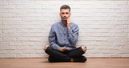 Young adult man sitting over white brick wall touching mouth with hand with painful expression because of toothache or dental illness on teeth. Dentist concept.