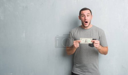 Photo for Young caucasian man over grey grunge wall showing one dollar scared in shock with a surprise face, afraid and excited with fear expression - Royalty Free Image