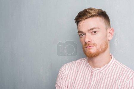 Photo pour Jeune homme rousse sur le mur gris grunge avec une expression confiante sur la pensée intelligente du visage sérieux - image libre de droit