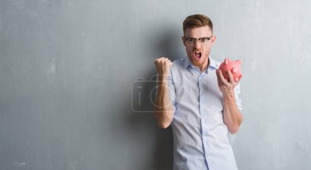 Young redhead man over grey grunge wall holding piggy bank annoyed and frustrated shouting with anger, crazy and yelling with raised hand, anger concept