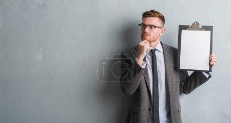 Photo pour Jeune homme d'affaires rousse sur le mur gris grunge tenant presse-papiers visage sérieux penser à la question, idée très confuse - image libre de droit