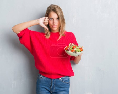Beautiful young woman over grunge grey wall eating tomato salad with angry face, negative sign showing dislike with thumbs down, rejection concept