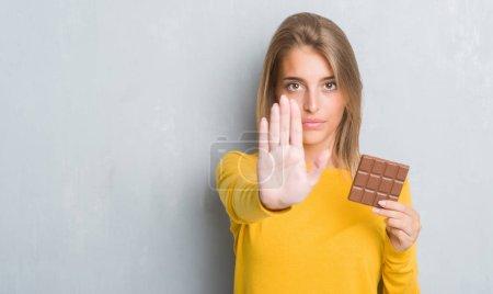 Photo pour Belle jeune femme trop grunge mur gris manger Mini-tablette de chocolat avec une main ouverte faisant signe d'arrêt avec l'expression grave et confiante, geste de défense - image libre de droit