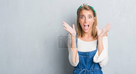 Photo for Beautiful young woman standing over grunge grey wall very happy and excited, winner expression celebrating victory screaming with big smile and raised hands - Royalty Free Image