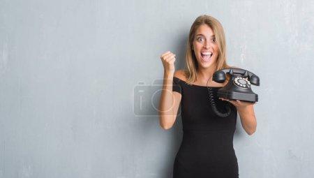 Photo pour Belle jeune femme sur le mur gris grunge tenant le téléphone vintage criant fier et célébrant la victoire et le succès très excité, acclamant l'émotion - image libre de droit