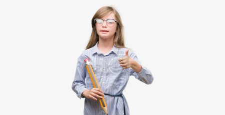 Young blonde child holding big pencil happy with big smile doing ok sign, thumb up with fingers, excellent sign