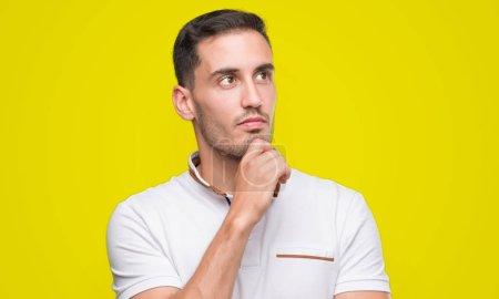 Photo pour Beau jeune homme décontracté portant un t-shirt blanc visage sérieux réfléchissant à la question, idée très confuse - image libre de droit