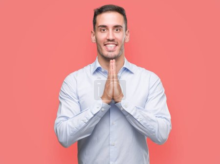 Handsome young businessman praying with hands together asking for forgiveness smiling confident.