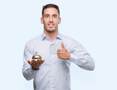 Handsome young man holding hotel ring bell happy with big smile doing ok sign, thumb up with fingers, excellent sign