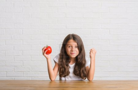 Photo for Young hispanic kid sitting on the table eating fresh tomato screaming proud and celebrating victory and success very excited, cheering emotion - Royalty Free Image