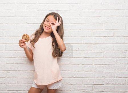Jeune garçon hispanique sur mur de briques blanches, manger du chocolat chips cooky avec visage heureux souriant faisant signe OK avec la main sur les yeux regardant à travers les doigts