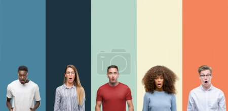 Group of people over vintage colors background afraid and shocked with surprise expression, fear and excited face.