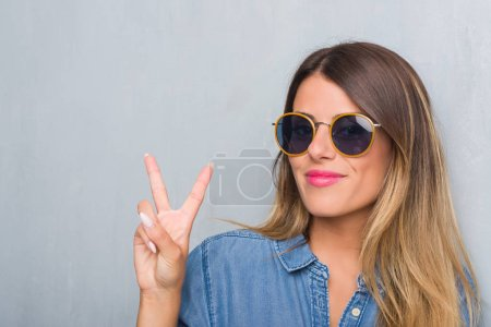 Photo for Young adult woman over grunge grey wall wearing retro sunglasses smiling with happy face winking at the camera doing victory sign. Number two. - Royalty Free Image
