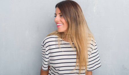 Young adult woman over grunge grey wall wearing navy t-shirt looking away to side with smile on face, natural expression. Laughing confident.