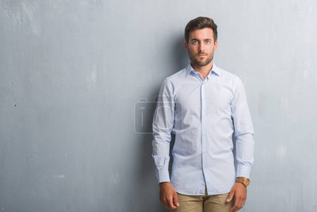 Handsome young business man over grey grunge wall wearing elegant shirt with serious expression on face. Simple and natural looking at the camera.