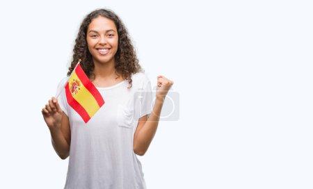 Photo pour Jeune femme hispanique tenant le drapeau de l'Espagne crier fier et célébrant la victoire et le succès très excité, acclamant l'émotion - image libre de droit