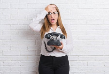 Young adult woman over white brick wall holding vintage telephone stressed with hand on head, shocked with shame and surprise face, angry and frustrated. Fear and upset for mistake.