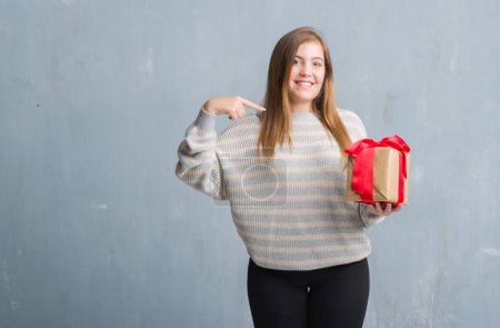 Photo pour Jeune femme adulte sur le mur gris grunge tenant un cadeau avec visage surprise pointant du doigt vers lui-même - image libre de droit
