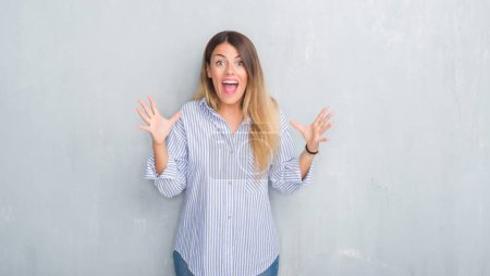 Photo for Young adult woman over grey grunge wall wearing fashion business outfit celebrating crazy and amazed for success with arms raised and open eyes screaming excited. Winner concept - Royalty Free Image