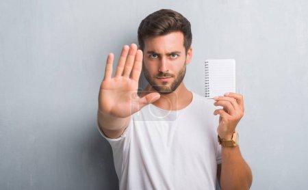 Photo pour Beau jeune homme sur gris grunge mur tenant blanc pour ordinateur portable avec la main ouverte, faisant signe d'arrêt avec une expression sérieuse et confiante, geste de défense - image libre de droit