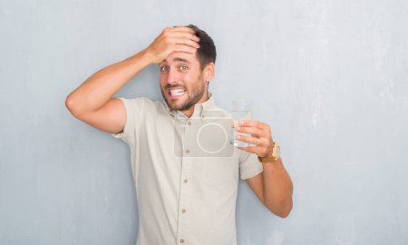 Handsome young man over grey grunge wall drinking glass of water stressed with hand on head, shocked with shame and surprise face, angry and frustrated. Fear and upset for mistake.