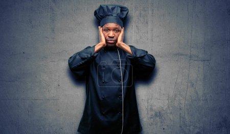 Photo pour Jeune cuisinier noir portant un chapeau de chef couvrant les oreilles ignorant le bruit bruyant ennuyeux, branche les oreilles pour éviter d'entendre le son. La musique bruyante est un problème . - image libre de droit