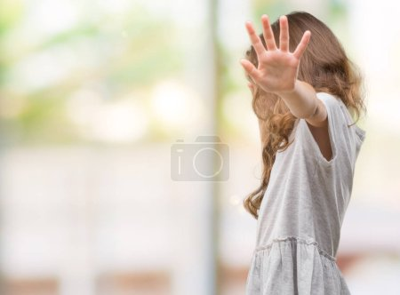Photo for Brunette hispanic girl wearing sunglasses covering eyes with hands and doing stop gesture with sad and fear expression. Embarrassed and negative concept. - Royalty Free Image
