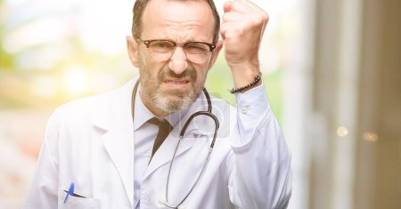 Photo for Doctor senior man, medical professional irritated and angry expressing negative emotion, annoyed with someone - Royalty Free Image