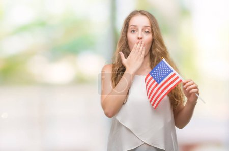 Photo for Young blonde woman holding flag of USA cover mouth with hand shocked with shame for mistake, expression of fear, scared in silence, secret concept - Royalty Free Image