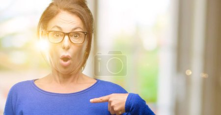 Middle age woman wearing wool sweater and glasses happy and surprised cheering expressing wow gesture, pointing with finger