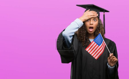 Young hispanic woman wearing graduation uniform holding flag of United States stressed with hand on head, shocked with shame and surprise face, angry and frustrated. Fear and upset for mistake.