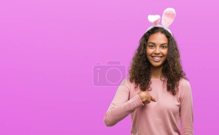 Young hispanic woman wearing easter bunny ears with surprise face pointing finger to himself