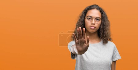 Beautiful young hispanic woman wearing glasses doing stop sing with palm of the hand. Warning expression with negative and serious gesture on the face.
