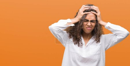 Beautiful young hispanic woman suffering from headache desperate and stressed because pain and migraine. Hands on head.