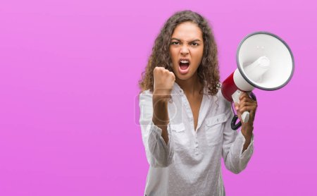 Young hispanic woman holding megaphone annoyed and frustrated shouting with anger, crazy and yelling with raised hand, anger concept
