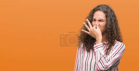 Beautiful young hispanic woman smelling something stinky and disgusting, intolerable smell, holding breath with fingers on nose. Bad smells concept.