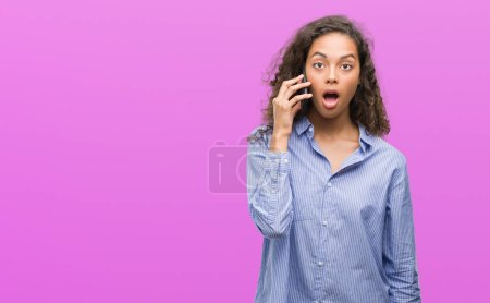 Young hispanic woman using smartphone scared in shock with a surprise face, afraid and excited with fear expression