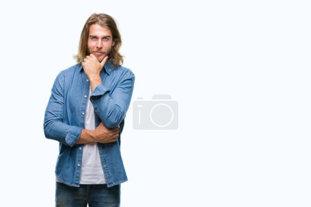 Young handsome man with long hair over isolated background looking confident at the camera with smile with crossed arms and hand raised on chin. Thinking positive.