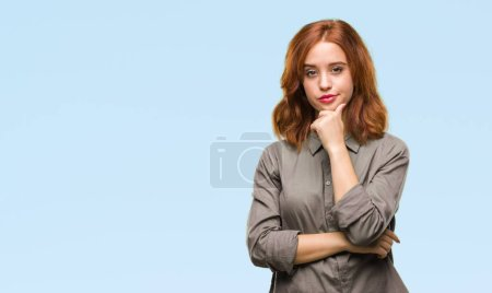 Young beautiful woman over isolated background looking confident at the camera with smile with crossed arms and hand raised on chin. Thinking positive.