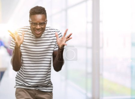 Photo for Young african american man wearing glasses and navy t-shirt celebrating crazy and amazed for success with arms raised and open eyes screaming excited. Winner concept - Royalty Free Image