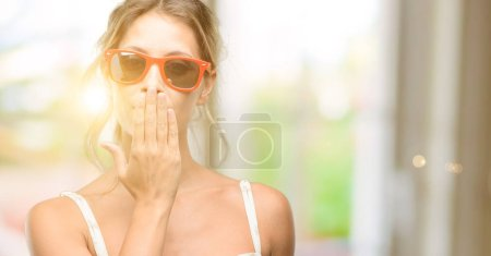 Young beautiful woman wearing red sunglasses covers mouth in shock, looks shy, expressing silence and mistake concepts, scared