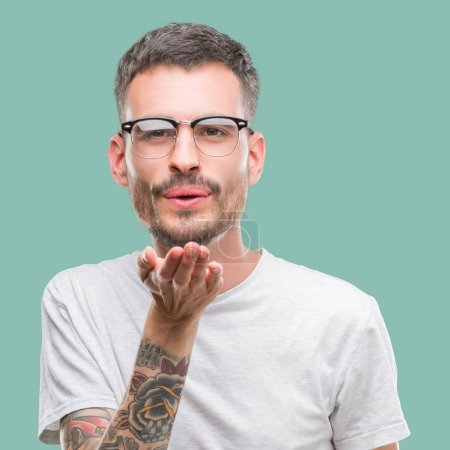 Young tattooed adult man looking at the camera blowing a kiss with hand on air being lovely and sexy. Love expression.