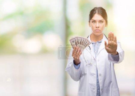 Photo pour Femme jeune médecin hisoire holding de dollars avec la main ouverte, faisant signe d'arrêt avec l'expression grave et confiante, geste de défense - image libre de droit