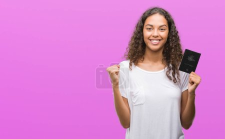 Photo for Young hispanic woman holding passport of Australia screaming proud and celebrating victory and success very excited, cheering emotion - Royalty Free Image