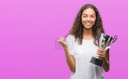 Young hispanic woman holding trophy screaming proud and celebrating victory and success very excited, cheering emotion