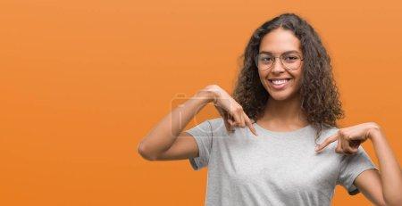 Photo pour Belle jeune femme hispanique portant des lunettes regardant confiant avec le sourire sur le visage, se montrant du doigt fier et heureux . - image libre de droit