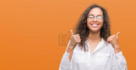 Photo pour Belle jeune femme hispanique signe de réussite faisant geste positif avec la main, pouces levés souriant et heureux. En regardant la caméra avec une expression joyeuse, geste gagnant . - image libre de droit