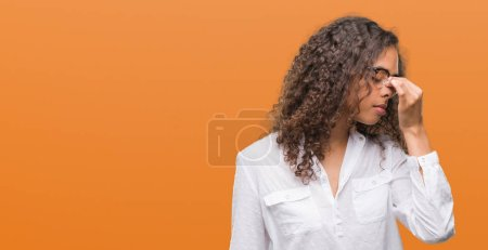 Beautiful young hispanic woman tired rubbing nose and eyes feeling fatigue and headache. Stress and frustration concept.