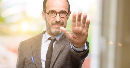 Photo pour Homme d'enseignant à l'aide de verres ennuyé avec mauvaise attitude faisant arrêt signe avec la main, dire non, exprimer la sécurité, de défense ou de restriction, poussant peut-être - image libre de droit